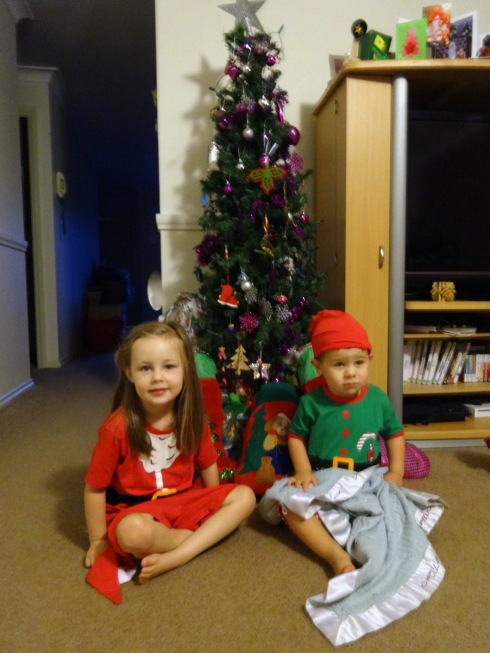 Hannah and Daniel groggily sit in front of the tree