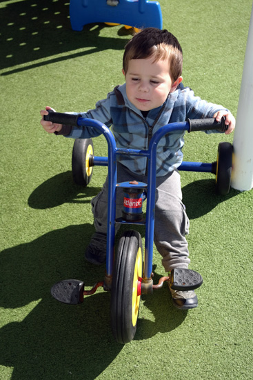 Daniel on one of the trikes in the outdoor area of the kids club.